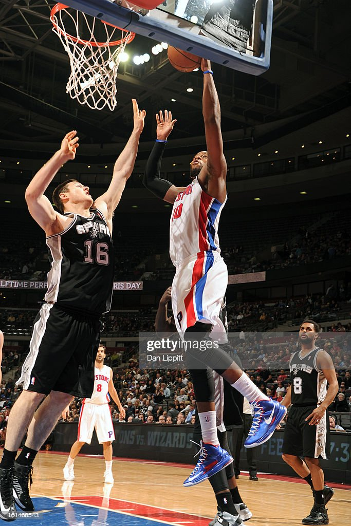 Greg Monroe #10 of the Detroit Pistons drives to the basket against Aron Baynes #16 of the San Antonio Spurs on February 8, 2013 at The Palace of Auburn Hills in Auburn Hills, Michigan.