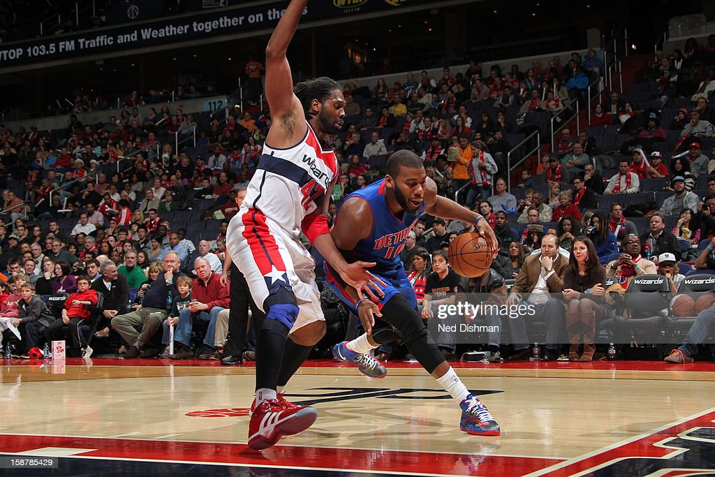 Greg Monroe #10 of the Detroit Pistons drives to the basket against Nene #42 of the Washington Wizards at the Verizon Center on December 22, 2012 in Washington, DC.