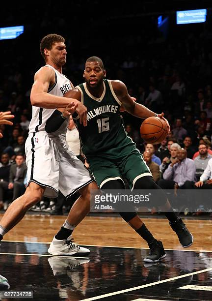 Greg Monroe of the Milwaukee Bucks dribbles against Brook Lopez of the Brooklyn Nets during their game at Barclays Center on December 1 2016 in New...