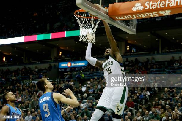 Greg Monroe of the Milwaukee Bucks dunks the ball past Yogi Ferrell and Nicolas Brussino of the Dallas Mavericks in the second quarter at BMO Harris...