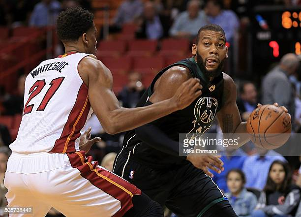 Greg Monroe of the Milwaukee Bucks is defended by Hassan Whiteside of the Miami Heat during a game at American Airlines Arena on January 19 2016 in...