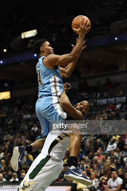 Greg Monroe of the Milwaukee Bucks is fouled by Gary Harris of the Denver Nuggets during the second half of a game at the BMO Harris Bradley Center...