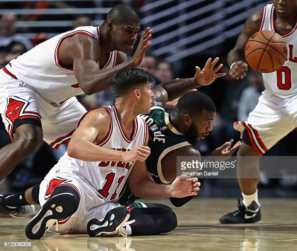 Greg Monroe of the Milwaukee Bucks passes the ball to a teammate surronded by Doug McDermott Cristiano Felicio and Isaiah Canaan of the Chicago Bulls...