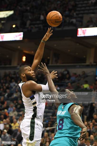 Greg Monroe of the Milwaukee Bucks shoots over Johnny O'Bryant III of the Charlotte Hornets during the first half of a game at the BMO Harris Bradley...