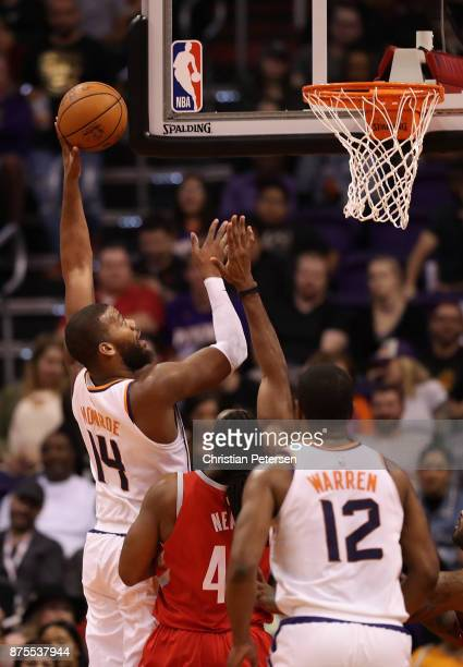 Greg Monroe of the Phoenix Suns attempts a shot over Nene Hilario of the Houston Rockets during the first half of the NBA game at Talking Stick...