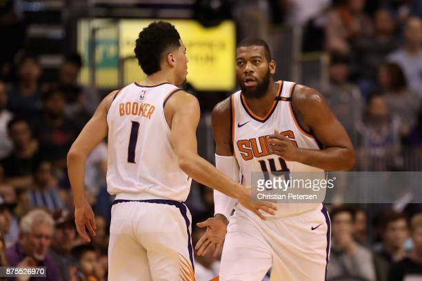 Greg Monroe of the Phoenix Suns high fives Devin Booker during the first half of the NBA game against the Houston Rockets at Talking Stick Resort...