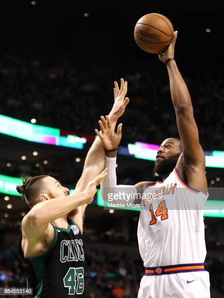 Greg Monroe of the Phoenix Suns takes a shot over Aron Baynes of the Boston Celtics during the second half at TD Garden on December 2 2017 in Boston...