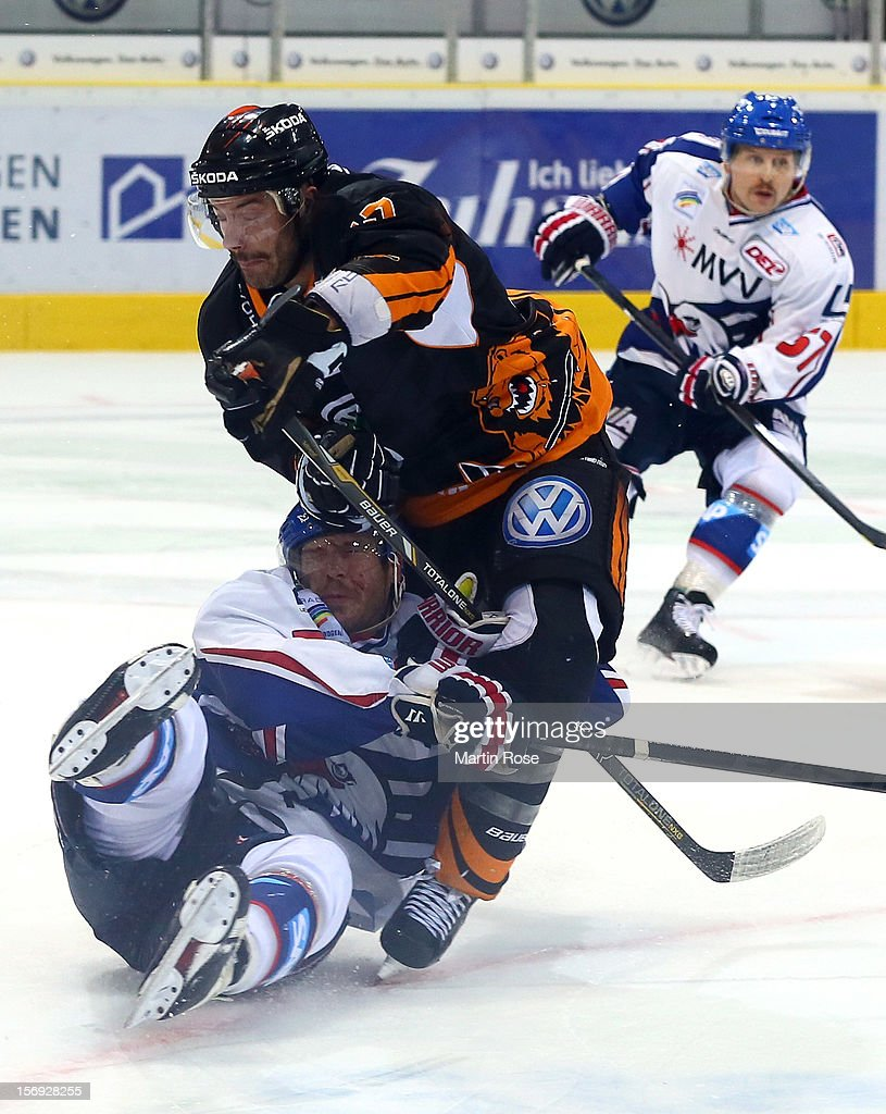 Greg Moore (R) of Wolfsburg battles for the puck with Nikolai Goc (L) of Mannheim during the DEL match between Wolfsburg Grizzly Adams and Adler Mannheim at Volksbank BraWo EisArena on November 25, 2012 in Wolfsburg, Germany.