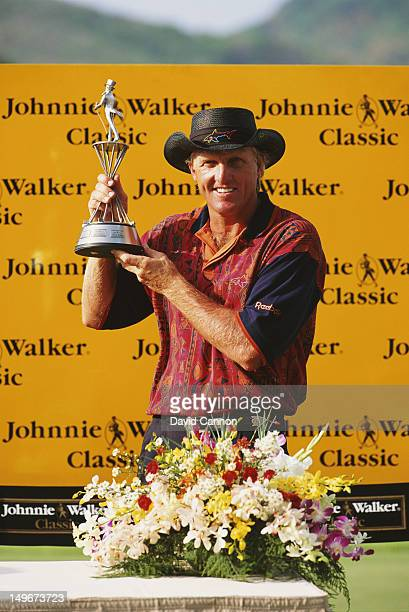 Greg Norman of Australia holds the trophy and celebrates winning the Johnnie Walker Classic on 6th February 1994 at the Blue Canyon Country Club in...