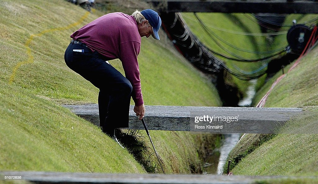 Greg Norman of Australia retrieves his ball on the 16th hole during the first round of the 133rd Open Championship at the Royal Troon Golf Club on...