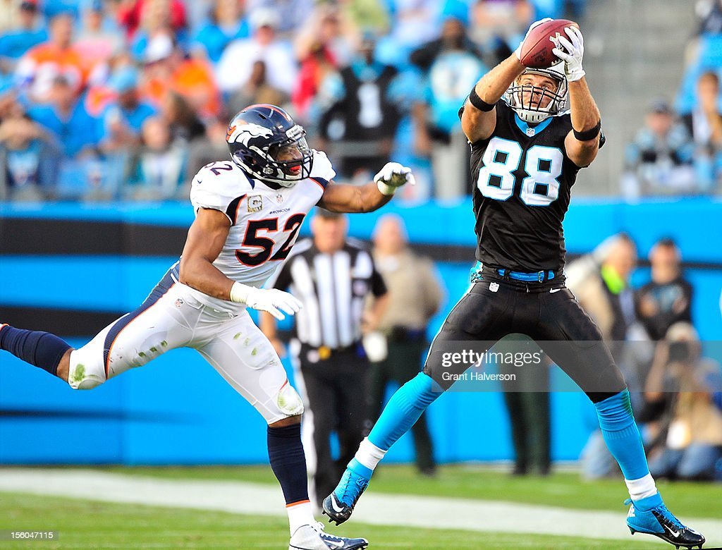 <a gi-track='captionPersonalityLinkClicked' href=/galleries/search?phrase=Greg+Olsen&family=editorial&specificpeople=2166920 ng-click='$event.stopPropagation()'>Greg Olsen</a> #88 of the Carolina Panthers makes a catch against defender <a gi-track='captionPersonalityLinkClicked' href=/galleries/search?phrase=Wesley+Woodyard&family=editorial&specificpeople=2190018 ng-click='$event.stopPropagation()'>Wesley Woodyard</a> #52 of the Denver Broncos during play at Bank of America Stadium on November 11, 2012 in Charlotte, North Carolina. The Broncos won 36-14.