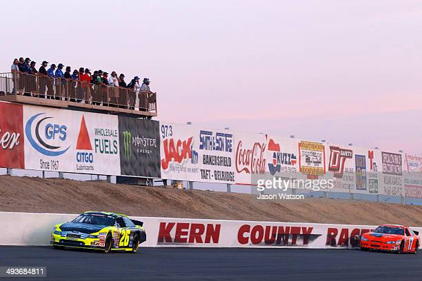 Greg Pursley driver of the Gene Price Motorsports/Star Nursery/Real Water Ford leads David Mayhew driver of the Steak Grape/MMI Services Chevrolet...