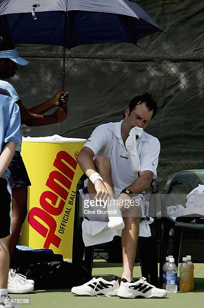 Greg Rusedski of Great Britain changes his socks on a change over against Thomas Johansson of Sweden during the NASDAQ100 Open at the Crandon Park...