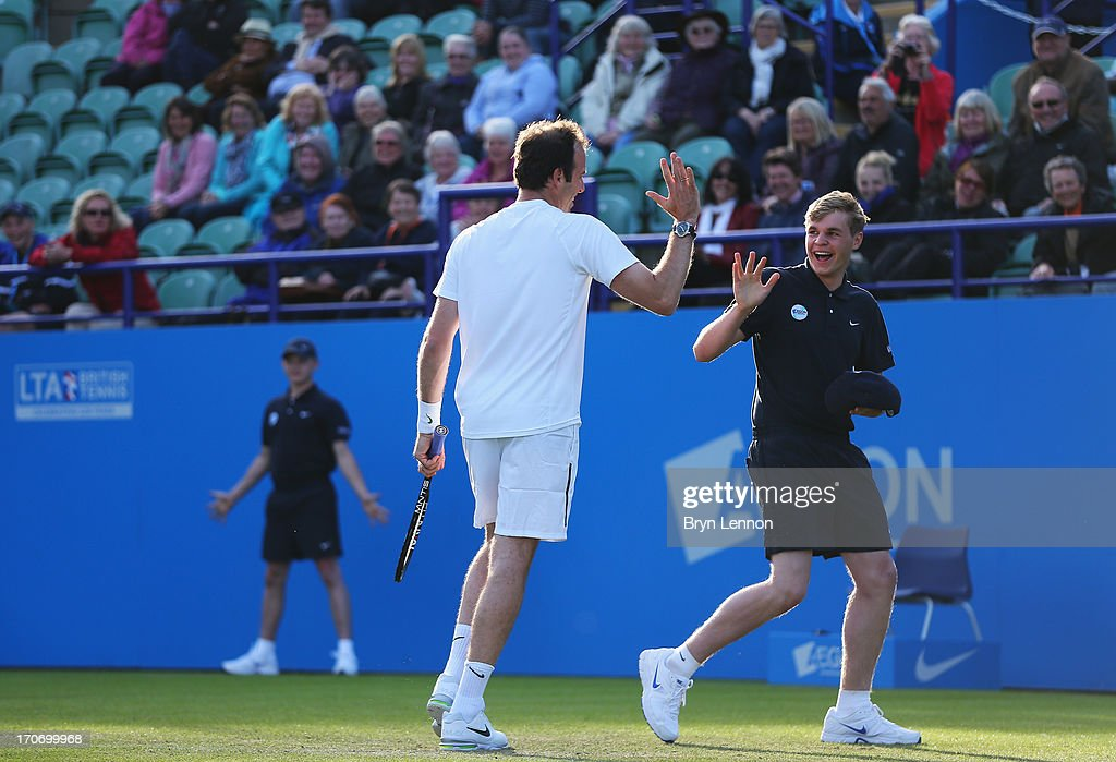 Greg Rusedski of Great Britain high fives a ball boy partnering Lindsay Davenport of USA in their mixed doubles exhibition legends match against Mark Philippoussis and Rennae Stubbs of Australia during day two of the AEGON International tennis tournament at Devonshire Park on June 16, 2013 in Eastbourne, England.
