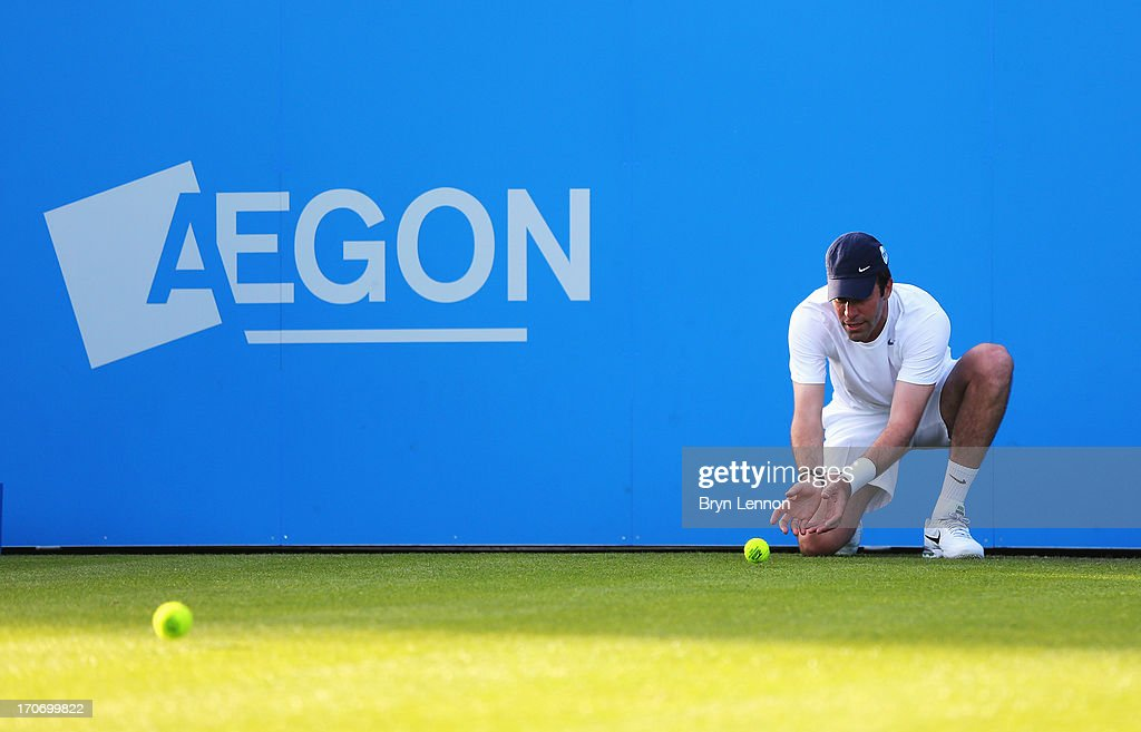 Greg Rusedski of Great Britain replaces the ball boy partnering Lindsay Davenport of USA in their mixed doubles exhibition legends match against Mark Philippoussis and Rennae Stubbs of Australia during day two of the AEGON International tennis tournament at Devonshire Park on June 16, 2013 in Eastbourne, England.