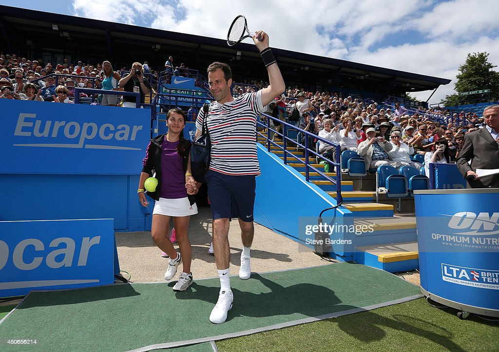<a gi-track='captionPersonalityLinkClicked' href=/galleries/search?phrase=Greg+Rusedski&family=editorial&specificpeople=201807 ng-click='$event.stopPropagation()'>Greg Rusedski</a> of Great Britain walks onto centre court with a young tennis fan before the Rally for Bally mixed doubles charity match on day two of the Aegon International at Devonshire Park on June 15, 2014 in Eastbourne, England.