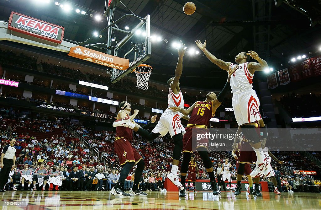 Greg Smith #4 and Thomas Robinson #41 of the Houston Rockets reach for a rebound against Marreese Speights #15 of the Cleveland Cavaliers at Toyota Center on March 22, 2013 in Houston, Texas.