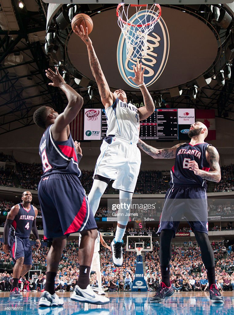 Greg Smith of the Dallas Mavericks puts up the layup against Pero Antic of the Atlanta Hawks on December 22 2014 at the American Airlines Center in...