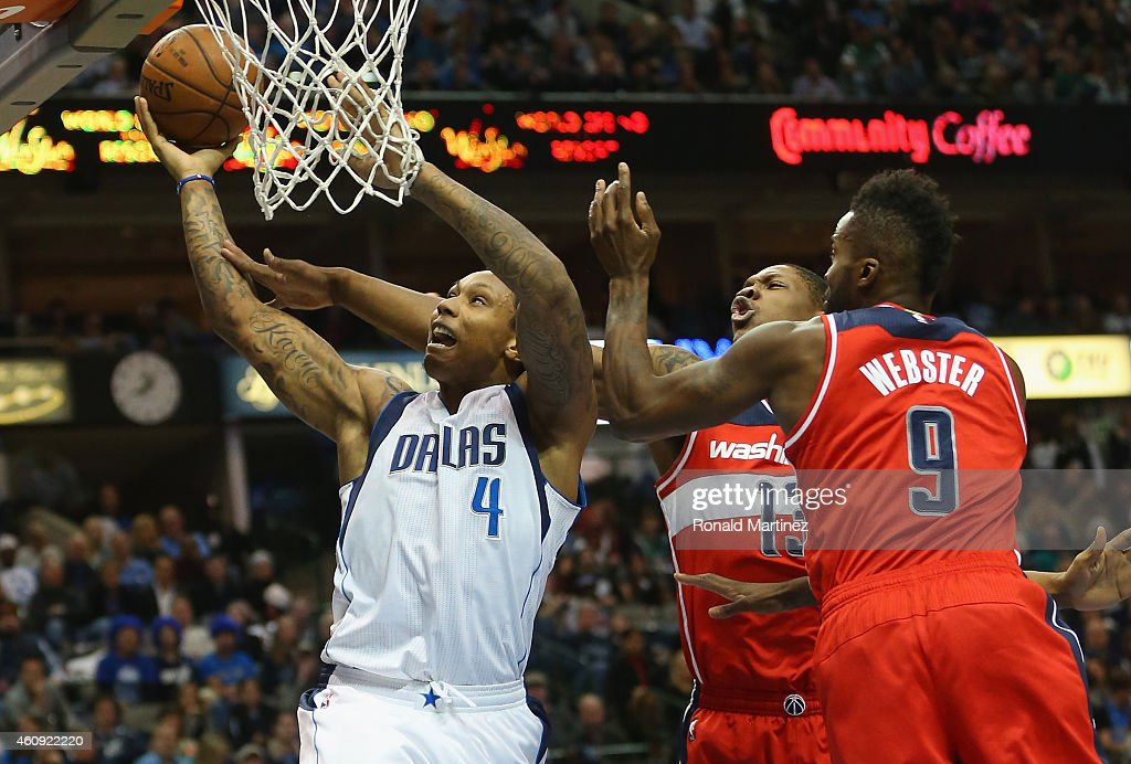 Greg Smith of the Dallas Mavericks takes a shot against Kevin Seraphin and Martell Webster of the Washington Wizards at American Airlines Center on...