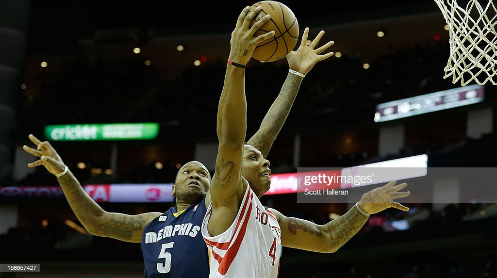 Greg Smith of the Houston Rockets drives against Marreese Speights of the Memphis Grizzlies at the Toyota Center on December 22 2012 in Houston Texas...