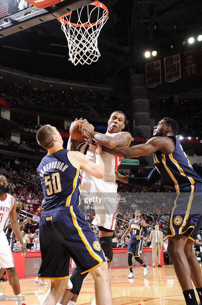 Greg Smith #4 of the Houston Rockets rebounds against <a gi-track='captionPersonalityLinkClicked' href=/galleries/search?phrase=Tyler+Hansbrough&family=editorial&specificpeople=642794 ng-click='$event.stopPropagation()'>Tyler Hansbrough</a> #50 and <a gi-track='captionPersonalityLinkClicked' href=/galleries/search?phrase=Ian+Mahinmi&family=editorial&specificpeople=740196 ng-click='$event.stopPropagation()'>Ian Mahinmi</a> #28 of the Indiana Pacers on March 27, 2013 at the Toyota Center in Houston, Texas.