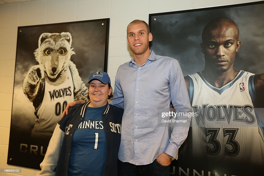 Greg Stiemsma of the Minnesota Timberwolves poses with a fan during the foundation jersey auction after the game between the Phoenix Suns and the...
