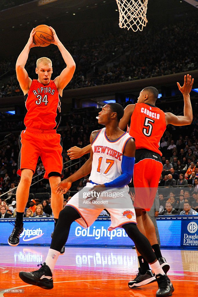 Greg Stiemsma of the Toronto Raptors rebounds over teammate Bruno Caboclo and Cleanthony Early of the New York Knicks in the second half at Madison...