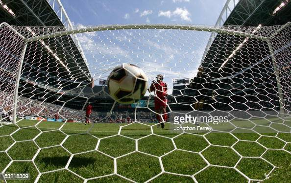 Greg Sutton and Kevin McKenna of Canada watch a ball headed by Landon Donovan of the United States land in the goal during the preliminary rounds of...