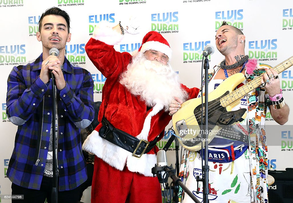 Greg T as Santa joins Joe Jonas (L) and Cole Whittle (R) of band DNCE when DNCE visits 'The Elvis Duran Z100 Morning Show' at Z100 Studio on November 18, 2016 in New York City.