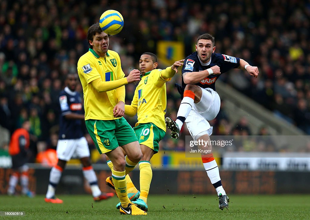Greg Taylor of Luton Town shoots at goal under pressure from Simeon Jackson of Norwich City during the FA Cup with Budweiser fourth round match between Norwich City and Luton Town at Carrow Road on January 26, 2013 in Norwich, England.