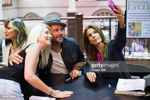 Greg Vaughan and Kristian Alfonso pose for a photo with a fan during the Days of Our Lives book signing at Barnes and Noble on October 29 2015 in...