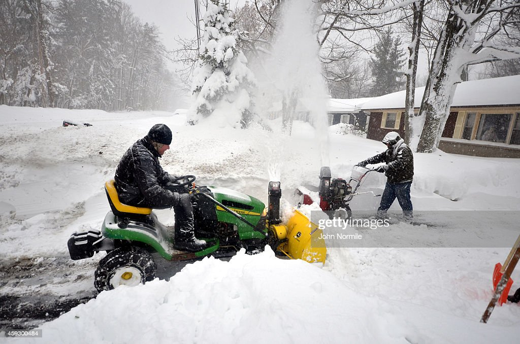 Greg waters and Mike Ostrander tries to remove some of the five feet of snow from a driveway on November 20 2014 in the Lakeview neighborhood of...