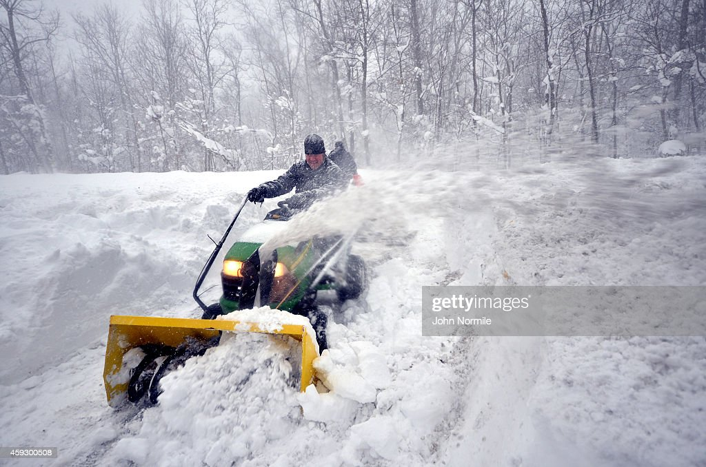 Greg Waters tries to remove some of the five feet of snow from a driveway on November 20 2014 in the Lakeview neighborhood of Buffalo New York The...
