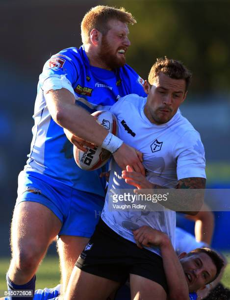 Greg Worthington of Toronto Wolfpack is tackled by Joe Bullock of Barrow Raiders during a Kingstone Press League 1 Super 8s match at Lamport Stadium...
