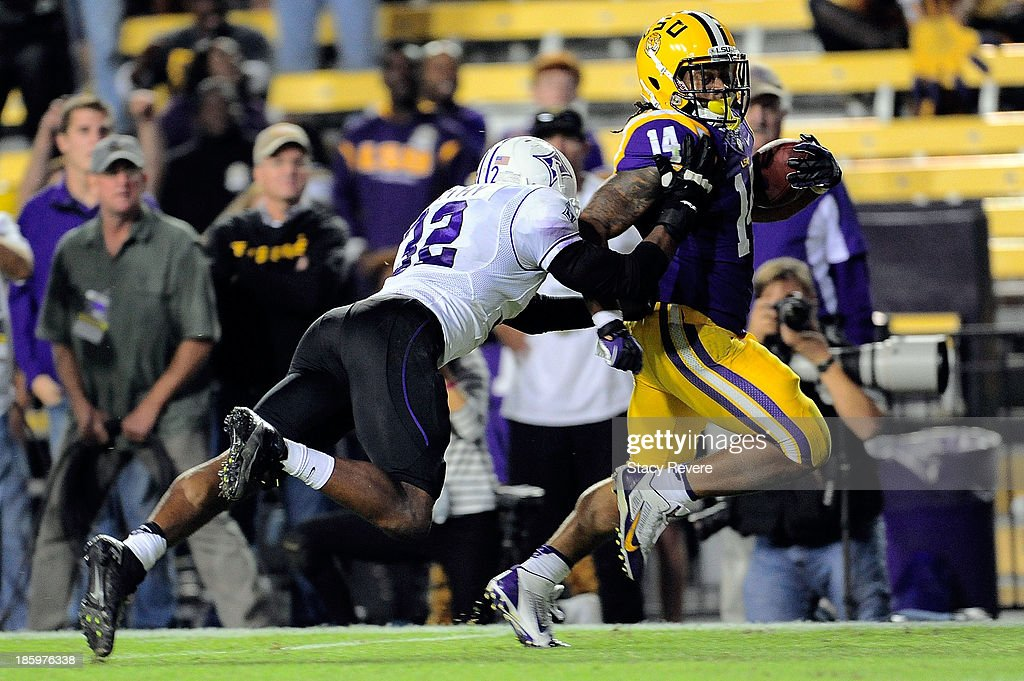 Greg Worthy #32 of the Furman Paladins dives for Terrence Magee #14 of the LSU Tigers during a game at Tiger Stadium on October 26, 2013 in Baton Rouge, Louisiana. LSU won the game 48-16.