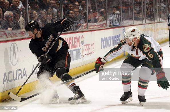 Greg Zanon of the Minnesota Wild reaches for the puck alongside the boards against Bobby Ryan of the Anaheim Ducks during the game on December 29...
