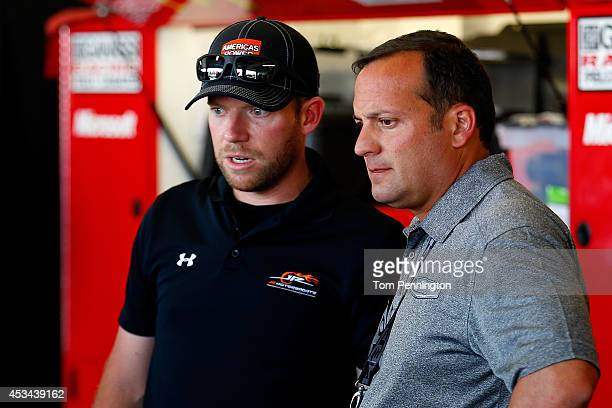 Greg Zipadelli StewartHaas Racing vice president of competition talks with Regan Smith driver of the Rush Truck Centers/Mobil 1 Chevrolet in the...
