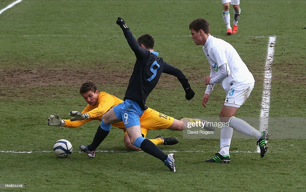 Grega Sorcan, the Slovenia goalkeeper saves at the feet of Bradley Fewster during the UEFA European Under 17 Championship match between England and Slovenia at Pirelli Stadium on March 28, 2013 in Burton-upon-Trent, England.