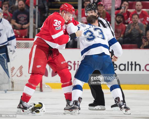 Gregg McKegg of the Tampa Bay Lightning drops gloves with Anthony Mantha of the Detroit Red Wings during an NHL game at Joe Louis Arena on March 24...