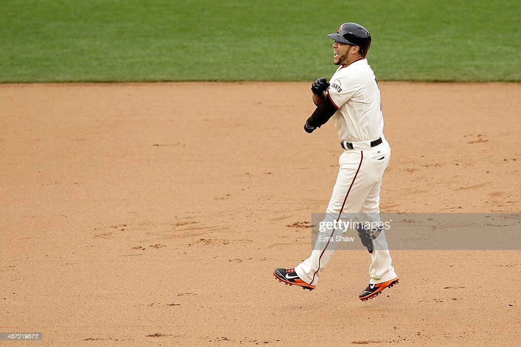 Gregor Blanco #7 of the San Francisco Giants and the Giants celebrate the 10th inning 5-4 victory against the St. Louis Cardinals during Game Three of the National League Championship Series at AT&T Park on October 14, 2014 in San Francisco, California.