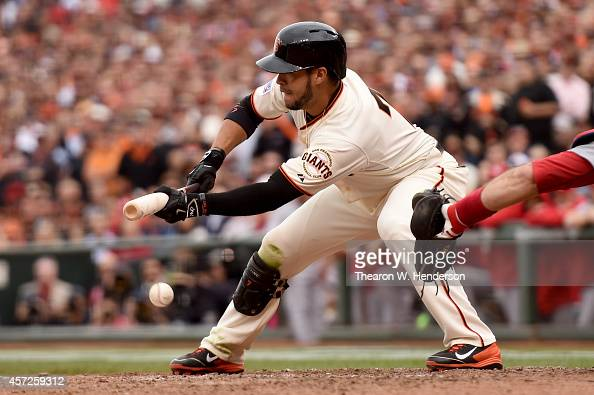 Gregor Blanco of the San Francisco Giants bunts the ball in the 10th inning to pitcher Randy Choate of the St Louis Cardinals during Game Three of...