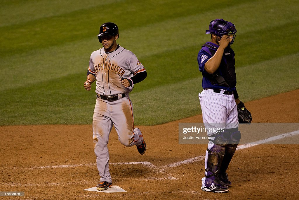 Gregor Blanco #7 of the San Francisco Giants crosses home plate as catcher Wilin Rosario #20 of the Colorado Rockies adjusts his mask during the seventh inning at Coors Field on August 27, 2013 in Denver, Colorado. The Giants defeated the Rockies 5-3.