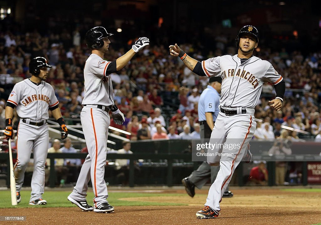 Gregor Blanco #7 of the San Francisco Giants high-fives Nick Noonan #21 after both scored runs against the Arizona Diamondbacks during the eighth inning of the MLB game at Chase Field on April 29, 2013 in Phoenix, Arizona.