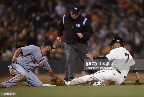 Gregor Blanco of the San Francisco Giants is tagged out at third base by Kevin Frandsen of the Washington Nationals in the bottom of the eighth...