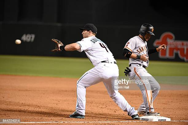 Gregor Blanco of the San Francisco Giants safely scrambles back to first base as Paul Goldschmidt of the Arizona Diamondbacks catches a throw from...