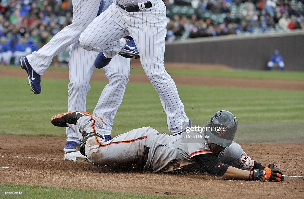 Gregor Blanco #7 of the San Francisco Giants slides safely into first base with a bunt single against the Chicago Cubs during the third inning on April 13, 2013 at Wrigley Field in Chicago, Illinois.