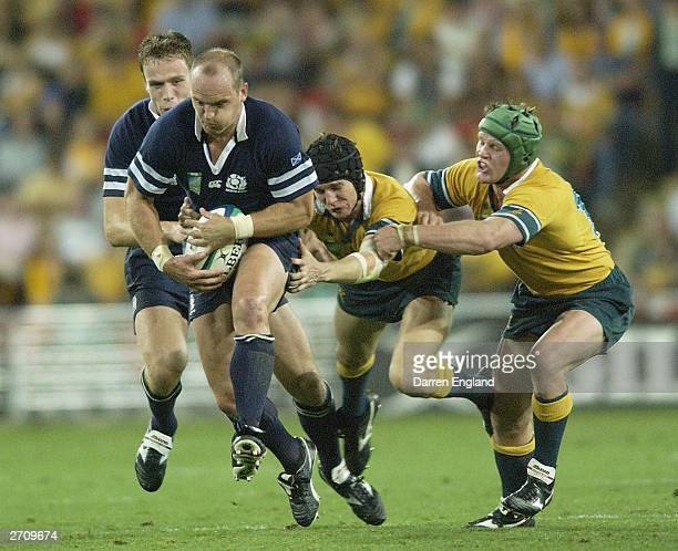 Gregor Townsend of Scotland is tackled by Stephen Larkham and Elton Flatley of Australia during the Rugby World Cup Quarter Final match between...