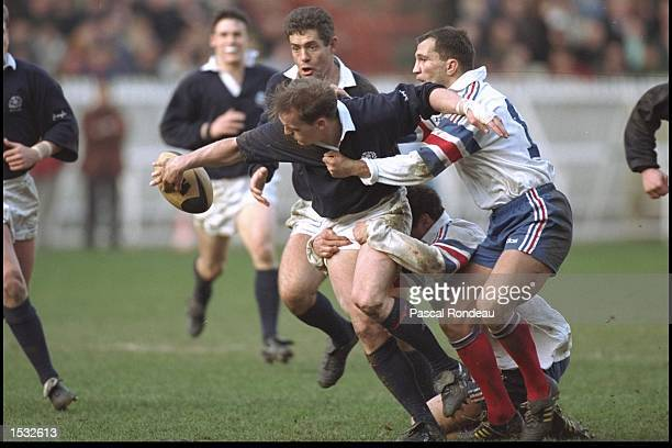Gregor Townsend of Scotland slips a try scoring pass to Gavin Hastings to set up a famous Scottish win over France at the Parc des Princes on...