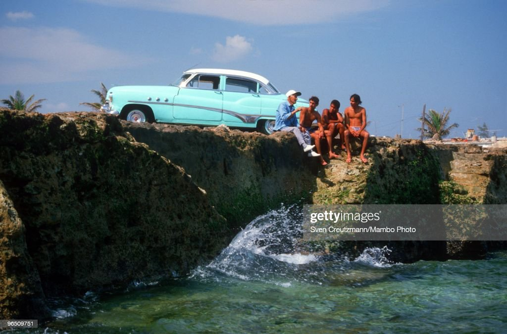 Gregorio Fuentes, former captain on Ernest Hemingway�s fishing boat Pilar, 91 years old, talks to Cuban youth as he sits next to an American Vintage car at the coast of the little fishermen village Cojimar, on November 20, 1988, In Havana, Cuba. Many say he was the inspiration for the protagonist in Hemingway's classic The Old Man and the Sea. Fuentes, born in Lanzarote, Canary Islands, on July 11, 1897, met Hemingway in 1928 and in the 1930s the writer hired him for USD 250 a month to care for his boat. Fuentes later inherited the Pilar but donated it to the Cuban government. The Pilar is now displayed in Hemingway�s former home, now a museum. Between 1939 and 1960, the American writer and journalist Ernst Hemingway lived for many years in Cuba. It was here where he wrote his novel The Old Man and the Sea, which earned him both the Pulitzer Prize and the Nobel Prize in Literature.