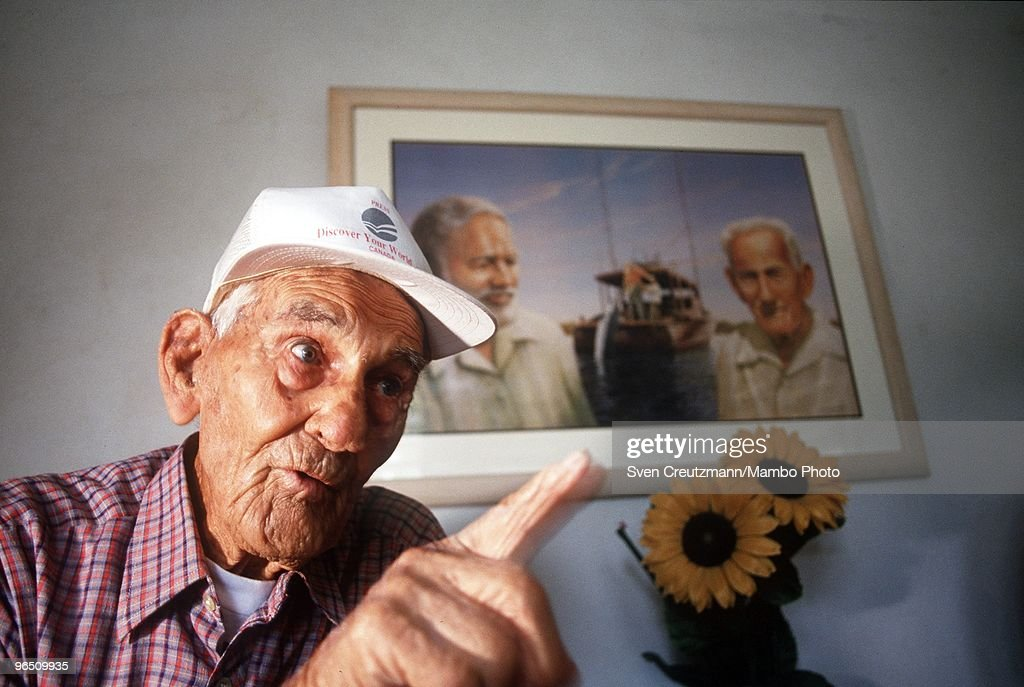 Gregorio Fuentes, former captain on Ernest Hemingway�s fishing boat Pilar, at the age of 100, gestures as he sits in his living room under a painting showing himself and Hemingway, in the little fishermen village Cojimar, on November 4, 1997, in Havana, Cuba. Many say he was the inspiration for the protagonist in Hemingway's classic The Old Man and the Sea. Fuentes, born in Lanzarote, Canary Islands, on July 11, 1897, met Hemingway in 1928 and in the 1930s the writer hired him for USD 250 a month to care for his boat. Fuentes later inherited the Pilar but donated it to the Cuban government. The Pilar is now displayed in Hemingway�s former home, now a museum. Between 1939 and 1960, the American writer and journalist Ernst Hemingway lived for many years in Cuba. It was here where he wrote his novel The Old Man and the Sea, which earned him both the Pulitzer Prize and the Nobel Prize in Literature.